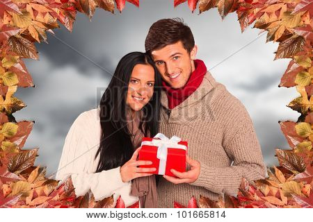 Young couple holding a gift against blue sky with clouds