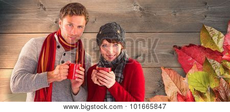 Couple both having warm drinks against bleached wooden planks background