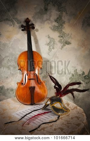 Violin With Score And Mask On A Stone Wall
