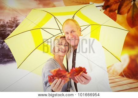 Happy mature couple showing autumn leaves under umbrella against autumn changing to winter