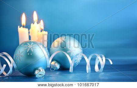Christmas balls with streamers and candles on blue background