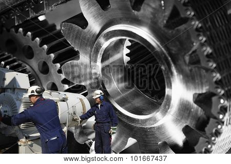 workers, mechanics with large cogwheels machinery, titanium and steel parts
