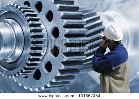industry worker, engineer pointing at giant cogwheels and gears parts