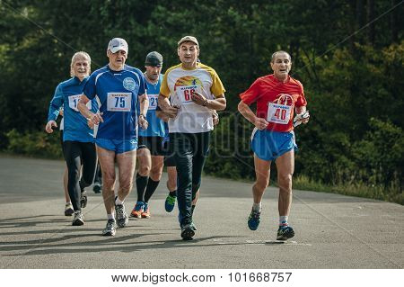 group of runners running down the road in Park