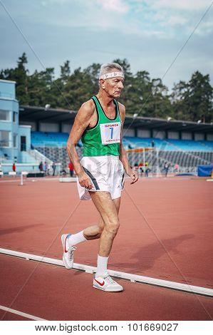 very old athlete running down the track stadium