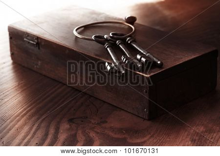 Old keys on a old wooden box. Shallow depth of field. Low key.