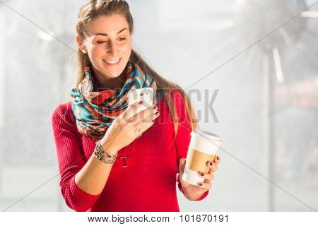 Woman at Fountain with Phone and coffee to takeaway