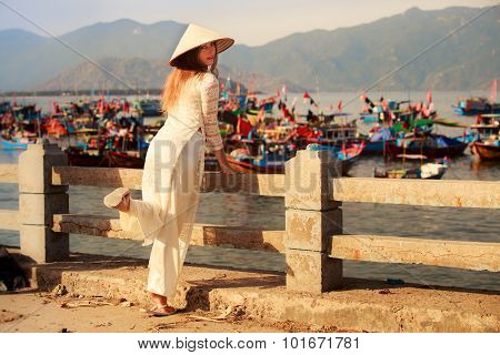Blonde Girl In Vietnamese Dress Leans On Barrier Turns Head