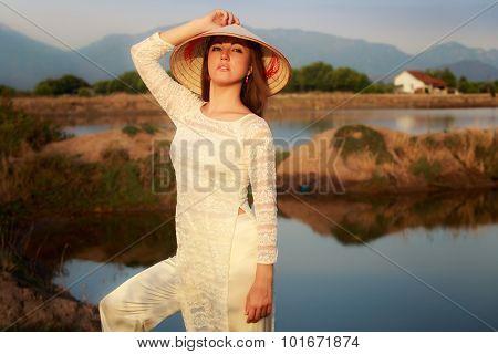 Girl In Vietnamese Hat Against Lakes Rocks Reflection