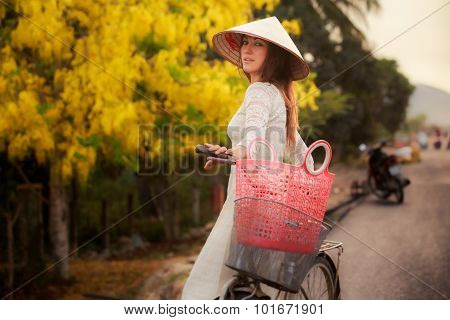Blonde Girl In Vietnamese And Hat By Bike Against Yellow Plant
