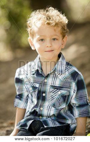 Cute little boy in a blue shirt at a park