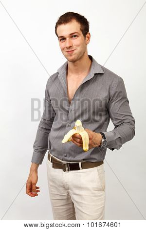Healthy nutrition - young man eating a banana