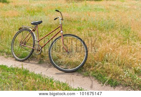 Rusty bicycle waiting for the master on the roadside