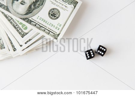 casino, gambling and fortune concept - close up of black dice and dollar cash money
