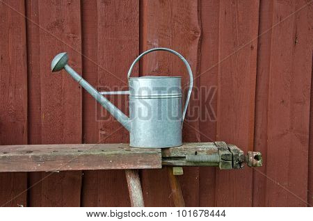 Metal Watering Can On Bench Besides Red Wooden Wall