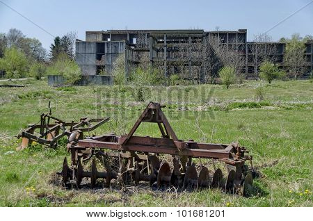 Abandoned unfinished building and farm machinery