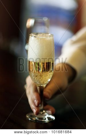 Bartender holding glass with champagne, close-up