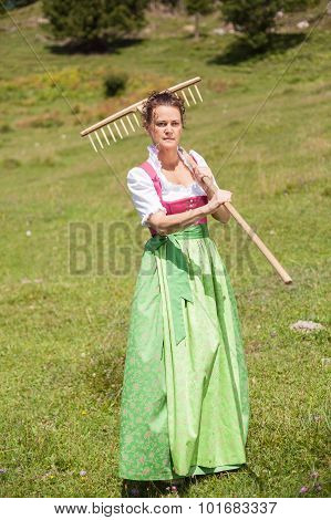 Woman In Dirndl In Middle Age With Meadow Flower In Mouth And Rake On His Shoulder