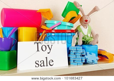 Toys for sale on shelf, on light wall background