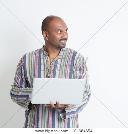 Portrait of mature casual business Indian man using laptop computer, looking at side copy space, standing on plain background with shadow.