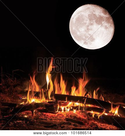 Flame of camp fire and big moon at night