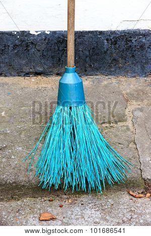 Abstract broom near house wall