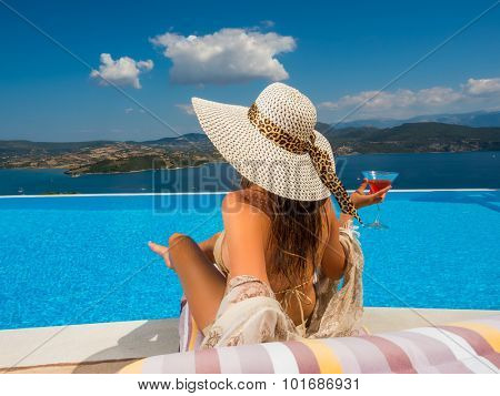 Woman holding a fresh cocktail relaxing by the infinity swimming pool in Greece