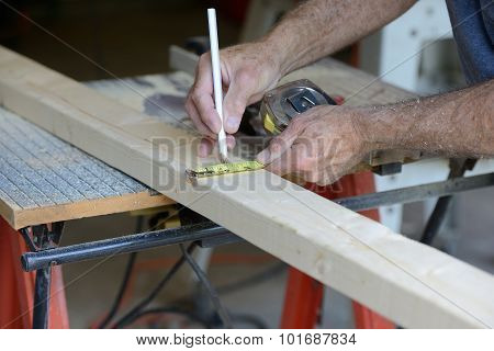 Worker Measuring Wood to Cut on Table Saw