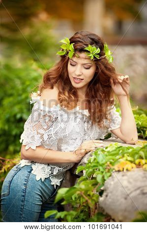 Young girl with wreath of green leaves, outdoors shot. Portrait of beautiful woman with long hair