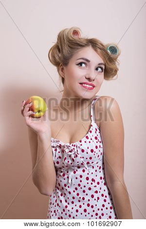 Funny amazed pin up girl in curlers with apple