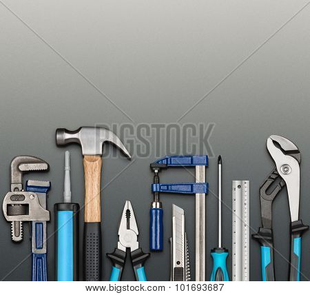 Various carpentry, repairing, DIY tools on softly grained gray background.