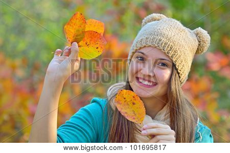 Happy girl with dry leaves  in forest