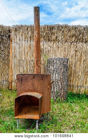 Traditional Rusty Metal Wood Oven In Backyard In A Sunny Summer Day