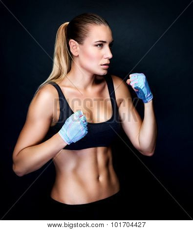 Boxer girl in action, isolated on black background, doing exercises in the studio, aggressive sport, healthy and active lifestyle