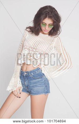 young hippie woman in sunglasses posing grimacing in studio