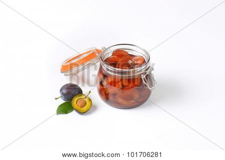 fresh plums and jar of preserved plums on white background