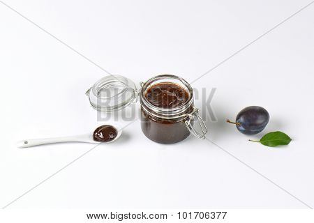 jar of fresh plum jam and ripe plum on white background