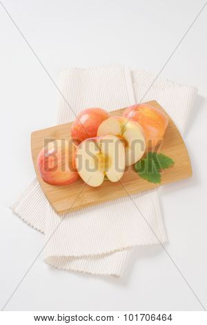 ripe apples on wooden cutting board and white place mat