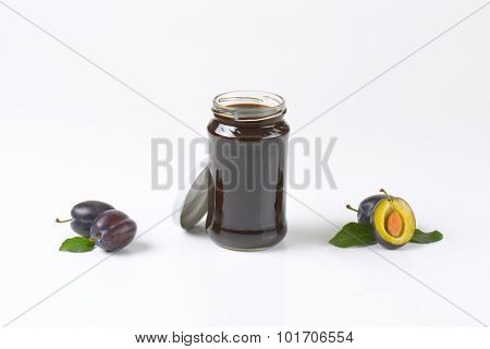 jar of fresh plum jam and ripe plums on white background