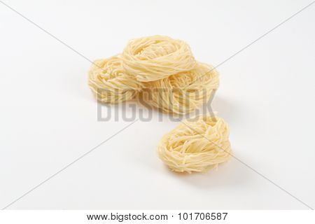 bundles of cooked noodles on white background