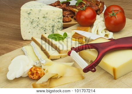 Slicing cheese, preparing for the home garden party. Fast food to wine and beer. Delicious canapes f