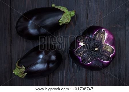 Eggplant (aubergine) on dark wooden table. Top view. Fresh raw farm vegetables - harvest from the ga