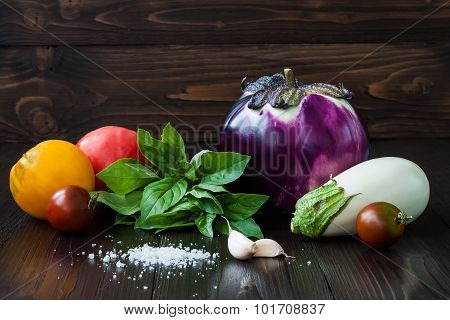 Purple and white eggplant (aubergine) with basil garlic and tomatoes on dark wooden table. Fresh raw