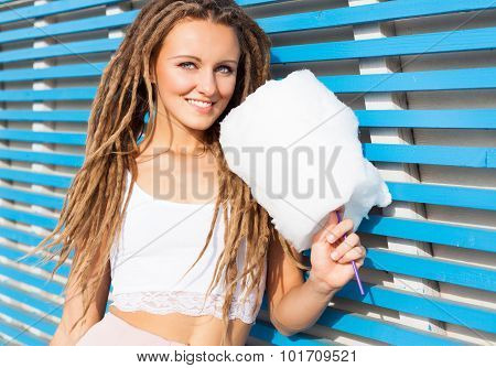 Beautiful young woman with dreads posing near blue plank wall with cotton candy summer warm evening.