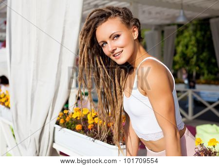 Beautiful young girl with dreadlocks in a summer cafe a sunny summer day