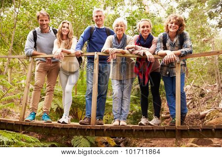 Multi-generation family on wooden bridge in forest, portrait
