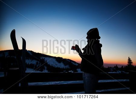 Apres ski, winter holiday - young woman drinking wine at sunset