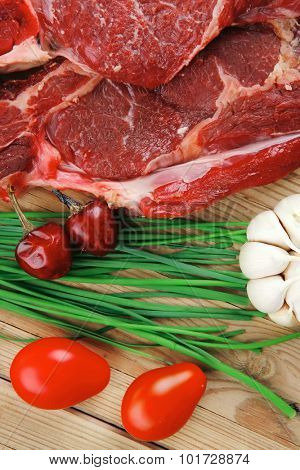 raw meat : boned fresh lamb ribs served with thyme , red chili pepper , cherry tomato , and green onion over wooden table