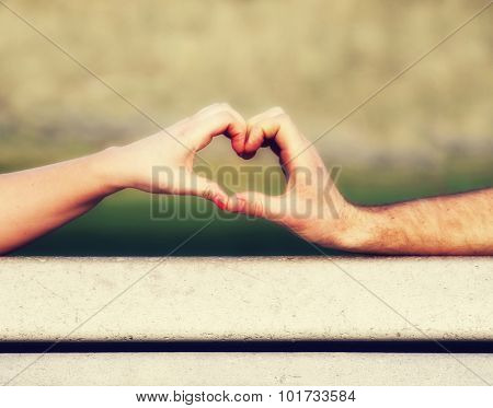 two people making a heart shape with their hands on a bench (shallow depth of field on the thumbs)