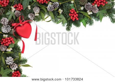 Christmas abstract background border with red heart bauble decoration, holly, ivy, mistletoe, pine cones and  blue spruce fir over white.